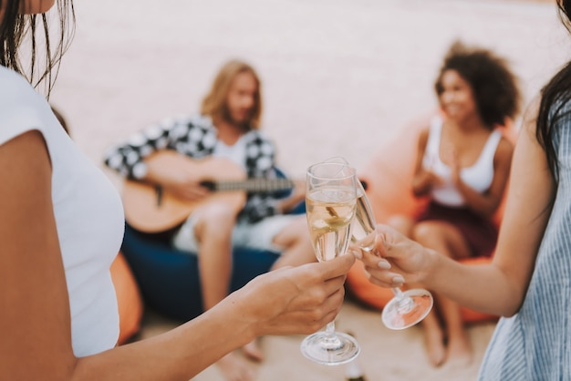 Beach party guitar playing champagne drinking. Premium Photo