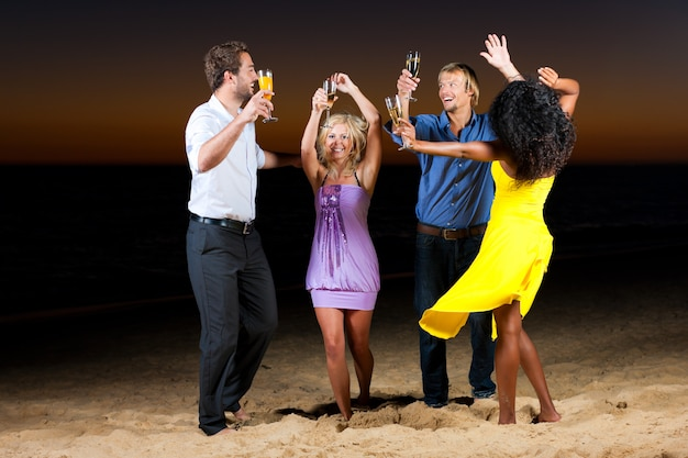 Beach party with friends dancing with drinks Premium Photo