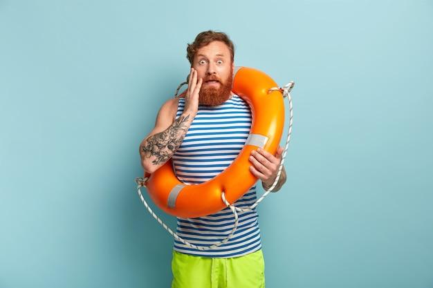 Lifebuoy와 함께 포즈를 취하는 해변 보호 남성 무료 사진