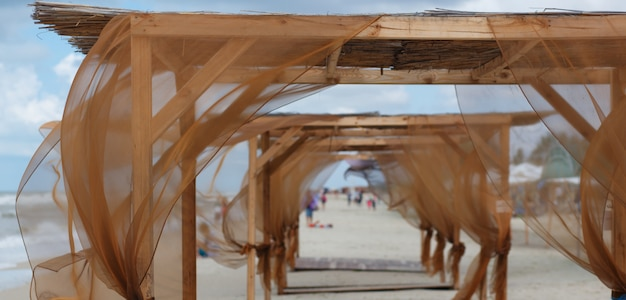 Beach sheds with brown curtains fluttering in the wind. Premium Photo