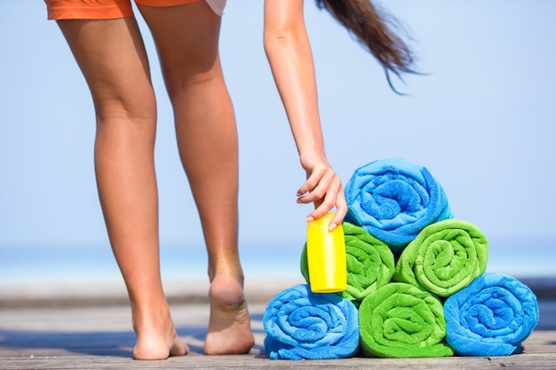 Beach and summer vacation accessories concept - close-up of colorful towels, hat, bag and sunblock Premium Photo
