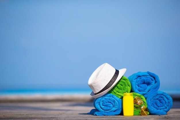 Beach and summer vacation accessories concept - close-up of colorful towels, hat and sunscreen Premium Photo
