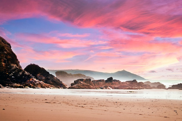 Beach surrounded by rocks and the sea under a cloudy sky during a beautiful pink sunset Free Photo
