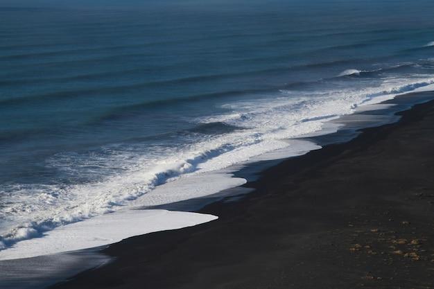 Spiaggia circondata dal mare sotto la luce del sole in islanda Foto Gratuite