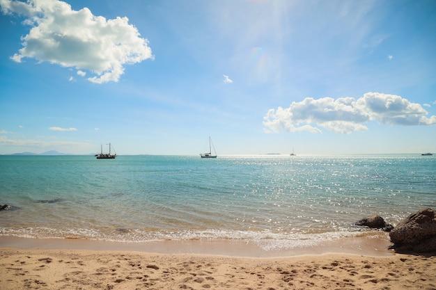 Spiaggia circondata dal mare con navi su di essa con le colline sotto la luce del sole Foto Gratuite