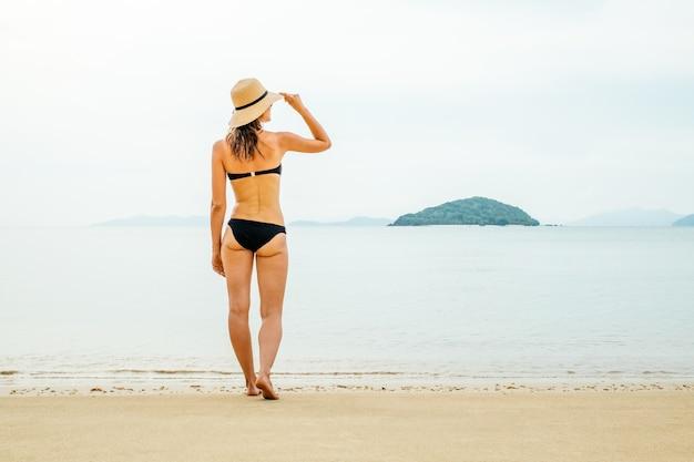 ビーチでの休暇。夏の日の海の景色を楽しみながらビーチに立っている日よけ帽とビキニの美しい女性 Premium写真