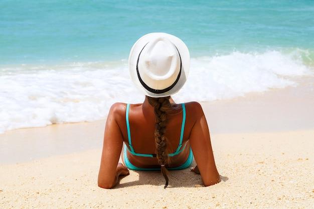 Beach vacation. slim beautiful woman in sunhat and blue bikini lying Premium Photo