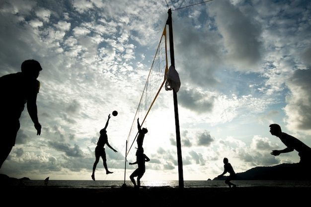 Beach volleyball team playing during sunset time Premium Photo