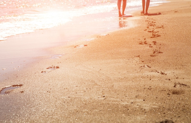 Beach, wave and women footprints at sunset time with sun flare Premium Photo
