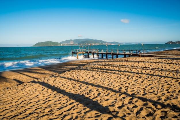 Beach with palm tree's shadows near ocean. pier with island behind Premium Photo