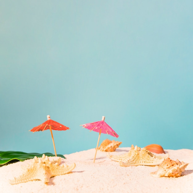 Beach with red sun umbrellas and starfishes Free Photo