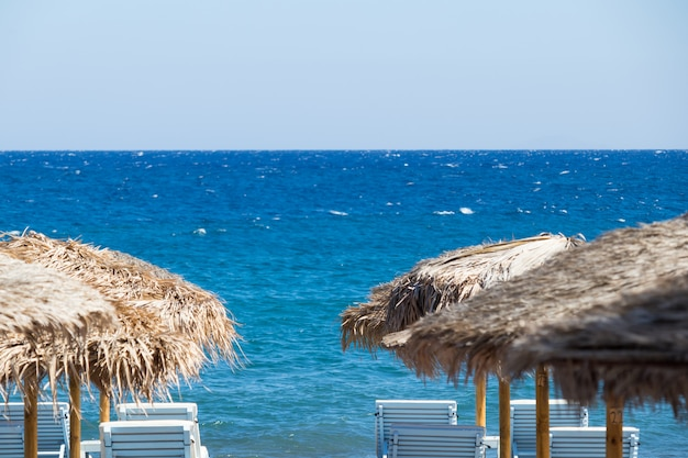 Beach with umbrellas and deck chairs by the sea in santorini Premium Photo