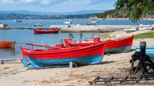 Spiaggiata barche colorate in legno sul costo del mar egeo, molo, yacht e colline a ouranopoli, grecia Foto Gratuite