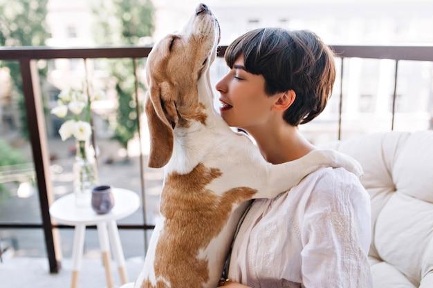 Il cane beagle alzò la testa e posò con le zampe sulle spalle della padrona Foto Gratuite