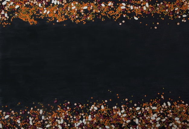 Beans, lentils, mung bean, peas are laid out on a black wooden background above and below Premium Photo