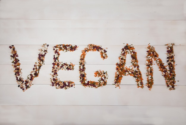 Beans, lentils, mung bean, peas laid out on a white wooden background in the form of the inscription vegan Premium Photo