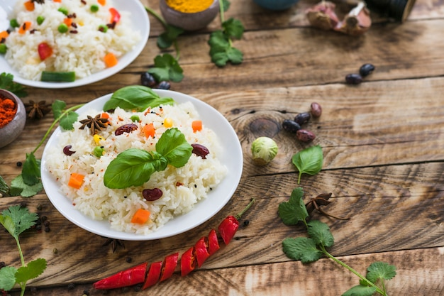 Beans rice and basil leaves on plate with organic ingredients on table Free Photo