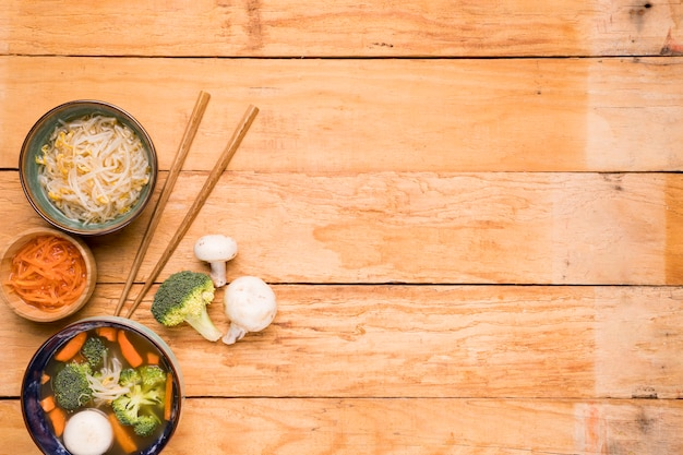 Beans sprout; carrot; and fish ball soup with chopsticks on wooden table Free Photo