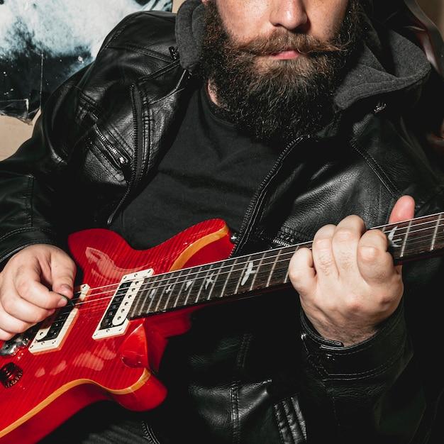 Beard man playing vintage red guitar Free Photo