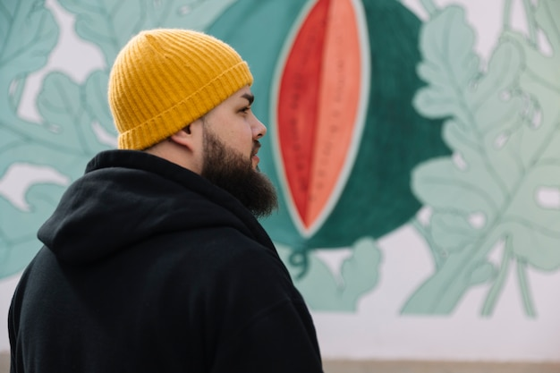 0e28df6942caa Beard man wearing knit hat standing in front of graffiti wall Free Photo