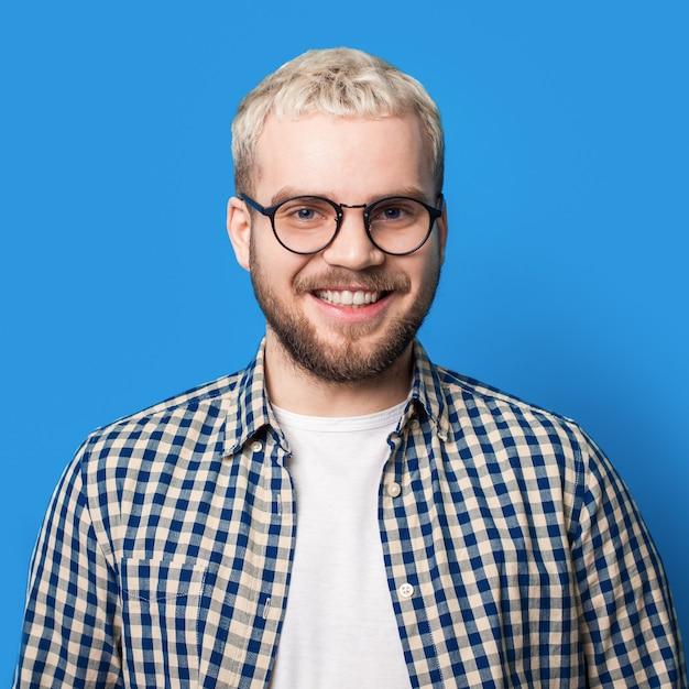 금발 머리와 파란색 스튜디오 벽에 카메라에 미소 안경 수염 남자 프리미엄 사진