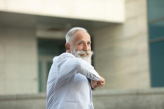 ひじで挨拶するひげの年配の男性 Premium写真