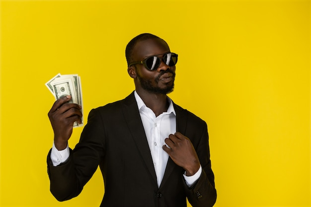 Bearded afroamerican guy is holding dollars in one hand, wearing sunglasses and black suit Free Photo