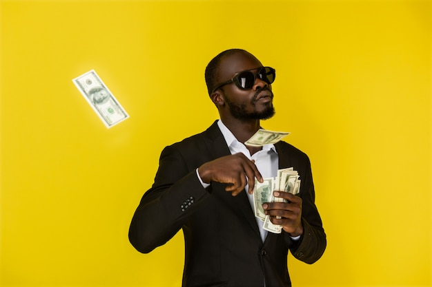 Bearded afroamerican guy is throwing out dollars from one hand, wearing sunglasses and black suit Free Photo