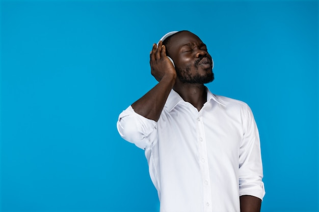 Bearded afroamerican man with closed eyes is holding by one hand big headphones in white shirt Free Photo