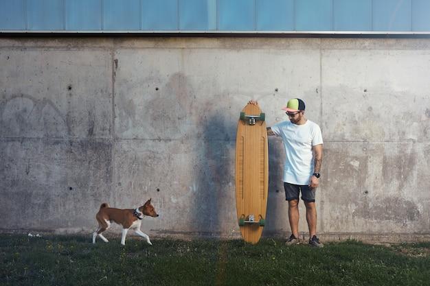 다가오는 갈색과 흰색 Basenji 개를보고있는 콘크리트 벽 옆에 서있는 수염과 문신을 한 Longboarder 무료 사진