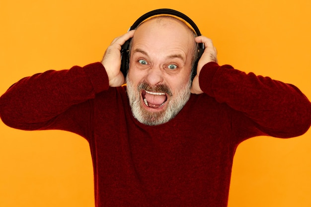 Бородатый сердитый разъяренный пенсионер в вязаном свитере широко открывает рот, разъяренный плохими новостями, слушает спортивную радиостанцию через беспроводные наушники bluetooth, громко кричит Бесплатные Фотографии