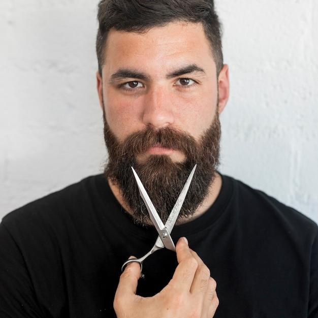Bearded barber holding scissors at hair salon Free Photo