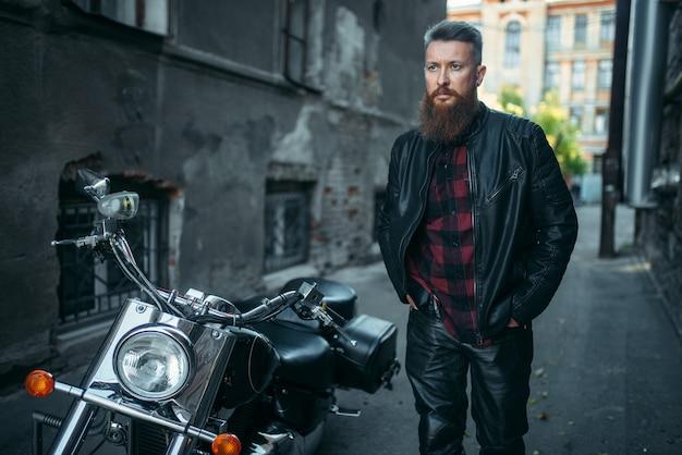 Бородатый байкер в кожаной одежде против своего вертолета. Premium Фотографии