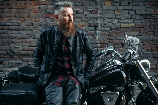 Бородатый байкер позирует на классическом чоппере, двухколесном транспорте. винтажный велосипедист на мотоцикле, образ жизни свободы Premium Фотографии