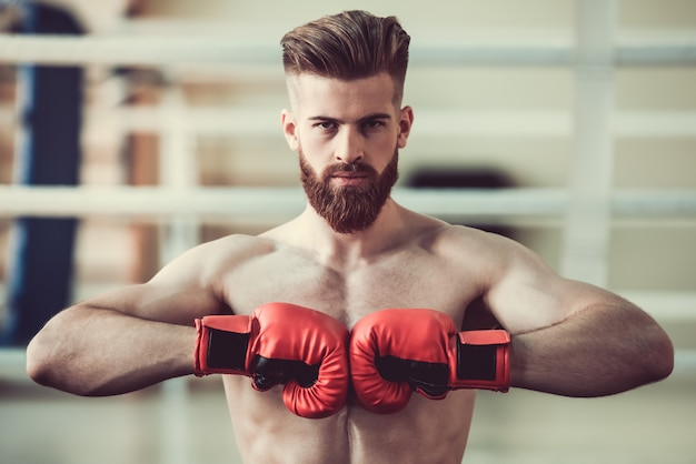 Bearded boxer with bare torso in red boxing gloves. Premium Photo
