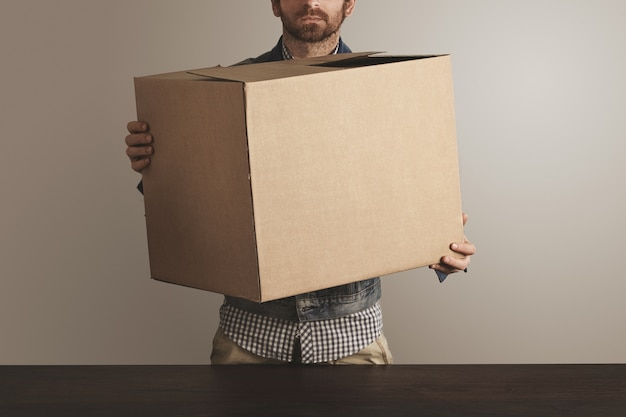Bearded brutal courier in jeans work jacket holds big carton paper box with goods above wooden table. Free Photo