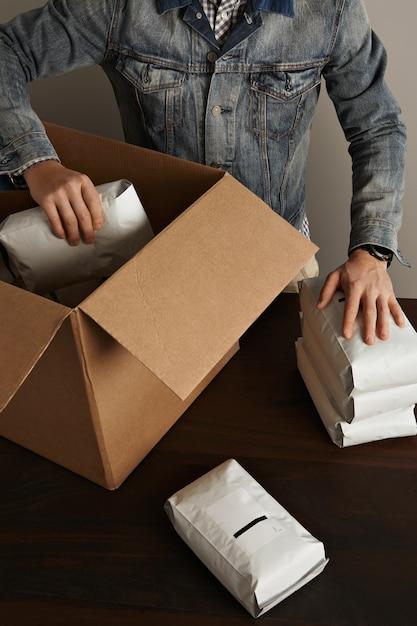ジーンズのワークジャケットのひげを生やした残忍な男は、木製のテーブルの大きなカートン紙箱の中に空白の密封された密閉パッケージを置きます。速達 無料写真