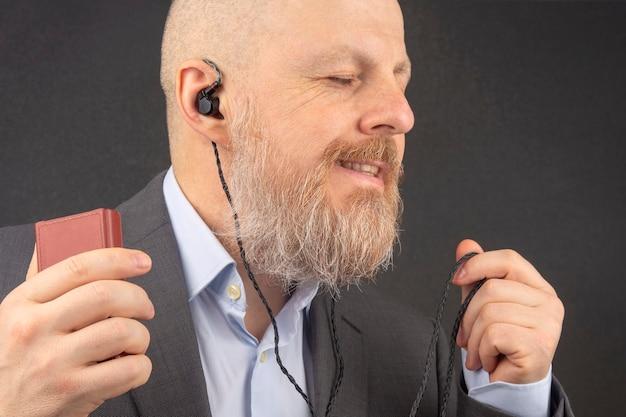 ひげを生やしたビジネスマンは、小さなヘッドホンでオーディオプレーヤーからお気に入りの音楽を聴くのを楽しんでいます。 Premium写真