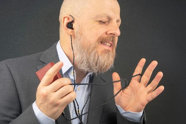 Бородатый деловой мужчина любит слушать свою любимую музыку через аудиоплеер в небольших наушниках. Premium Фотографии