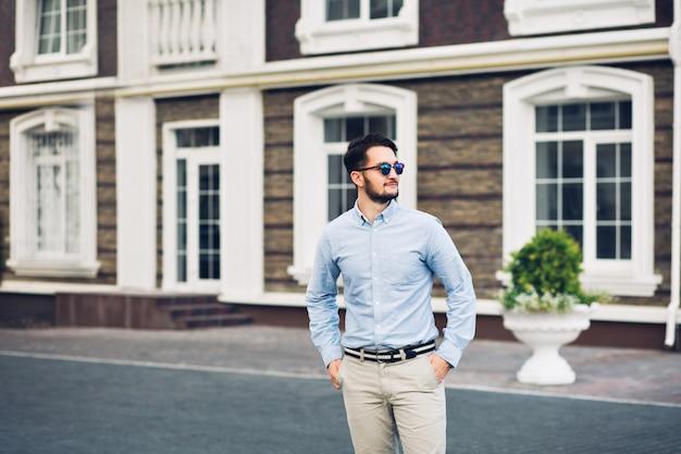 通りを歩いてサングラスのひげを生やした実業家。彼はポケットに手を入れて、遠くに笑っています。 無料写真