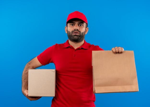 青い壁の上に立っている深刻な顔を持つ赤い制服とキャップ保持ボックスと紙のパッケージのひげを生やした配達人 無料写真