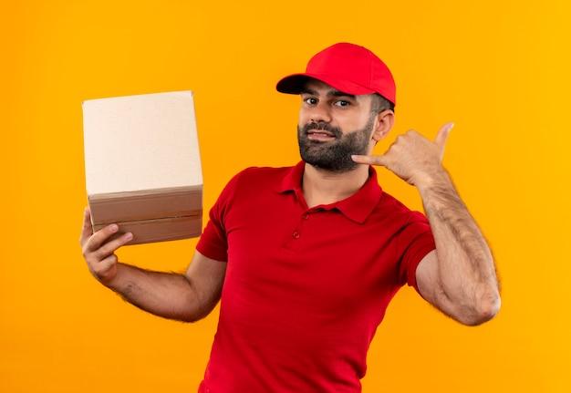 赤い制服とキャップ保持ボックスパッケージのひげを生やした配達人は、オレンジ色の壁の上に立って笑顔でジェスチャーを呼んで 無料写真