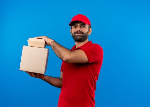 青い壁の上に立っている自信を持って笑顔でボックスパッケージを保持している赤い制服と帽子のひげを生やした配達人 無料写真