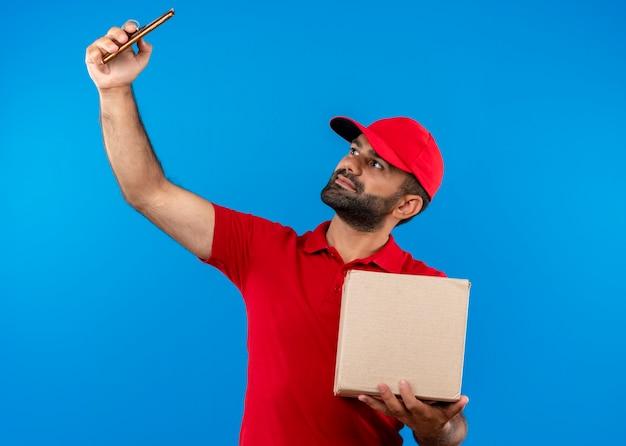 青い壁の上に立っている彼のスマートフォンを使用してselfieを撮る赤い制服とキャップ保持ボックスのひげを生やした配達人 無料写真