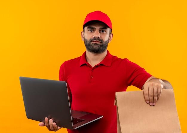 오렌지 벽 위에 서 심각한 얼굴로 종이 패키지와 노트북을 들고 빨간 유니폼과 모자 수염 배달 남자 무료 사진