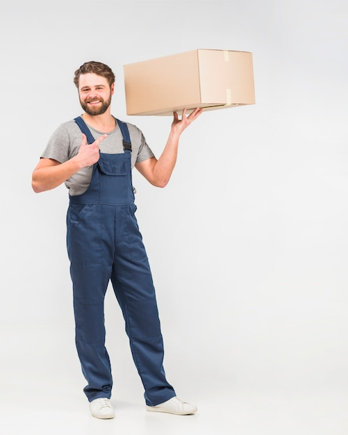Bearded delivery man pointing finger at box Free Photo