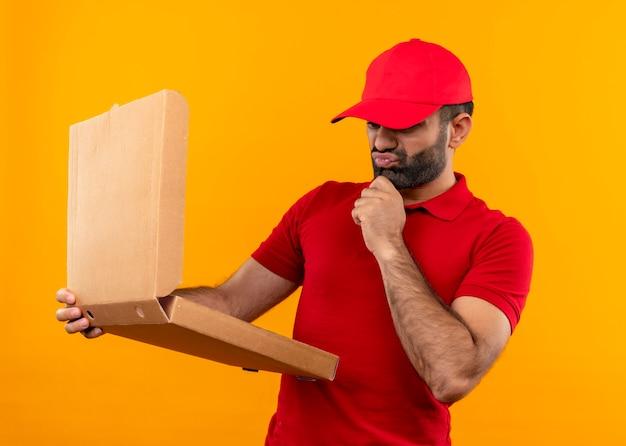 Uomo barbuto di consegna in uniforme rossa e cappuccio che tiene la scatola della pizza aperta guardandolo confuso e molto ansioso in piedi sopra il muro arancione Foto Gratuite