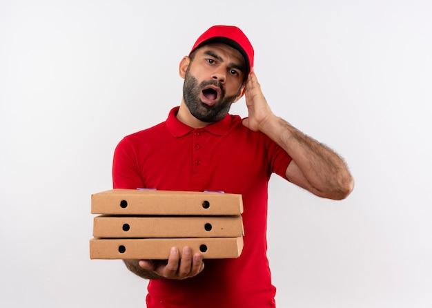 Uomo barbuto di consegna in uniforme rossa e cappuccio che tiene pila di scatole per pizza scioccato e confuso con la bocca spalancata in piedi sopra il muro bianco Foto Gratuite