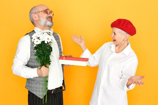 Бородатый пожилой джентльмен с лысой головой держит полевые цветы и коробку шоколадного подарка своей элегантной подруге средних лет на день святого валентина Бесплатные Фотографии