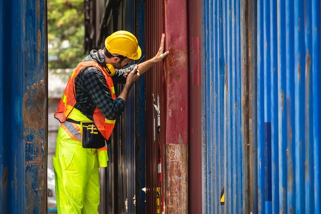 Bearded engineer standing with yellow helmet to control loading and check a quality of containers Premium Photo